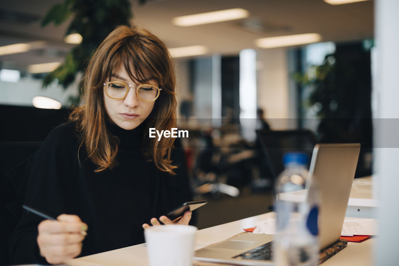 one person, glasses, real people, eyeglasses, young adult, front view, women, indoors, wireless technology, business, technology, adult, young women, communication, hairstyle, table, portrait, holding, hair, using laptop