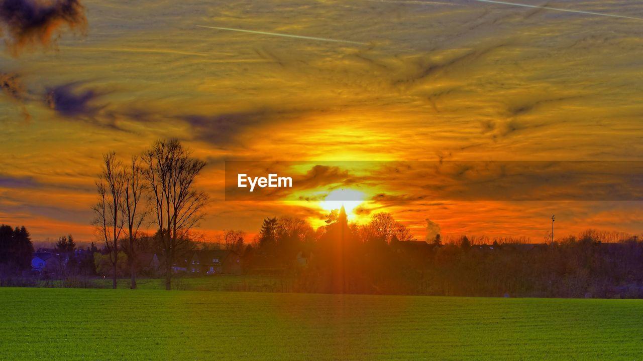 Idyllic Shot Of Dramatic Sky Over Green Landscape During Sunset