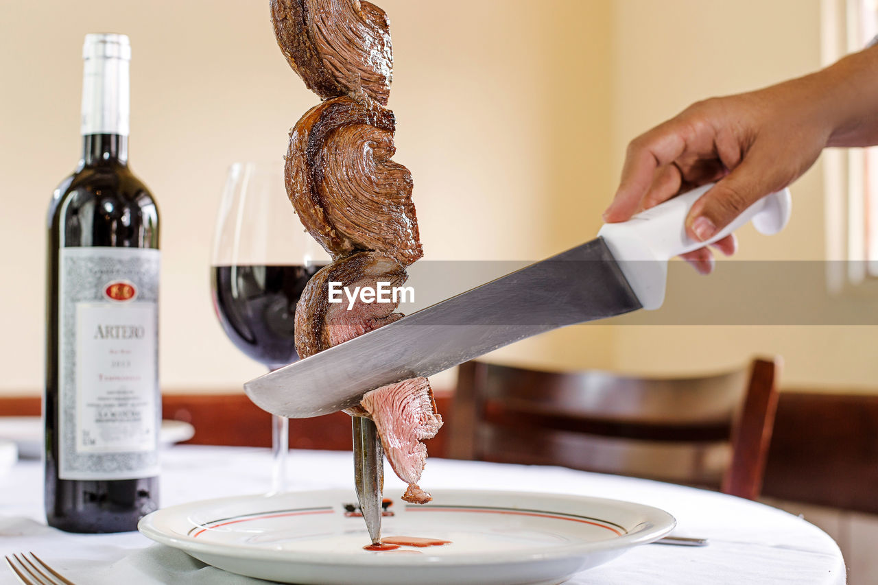 food and drink, food, human hand, human body part, indoors, hand, one person, real people, freshness, holding, preparation, lifestyles, drink, focus on foreground, table, meat, kitchen, container, close-up, preparing food, finger