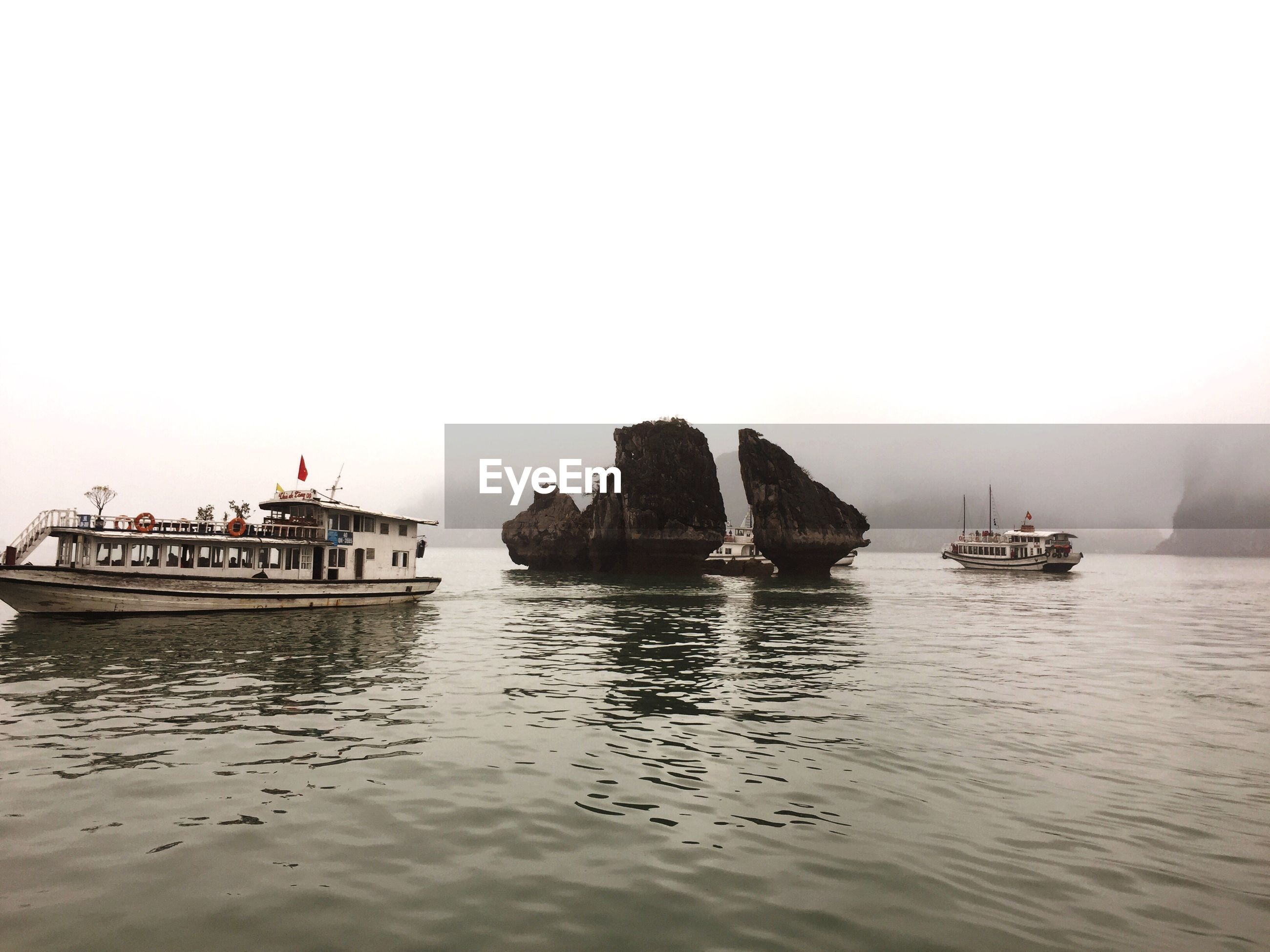 Scenic view of rock formations and boats at sea
