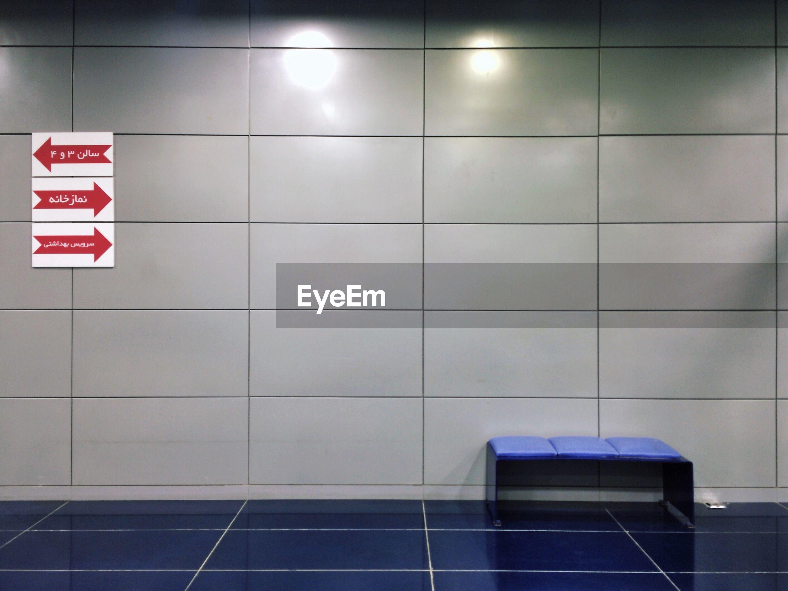INFORMATION SIGN ON TILED FLOOR IN ILLUMINATED ROOM