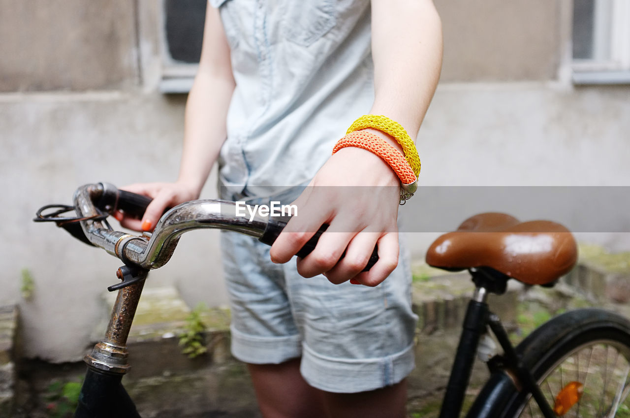 Midsection Of Woman With Bicycle Standing Outdoors