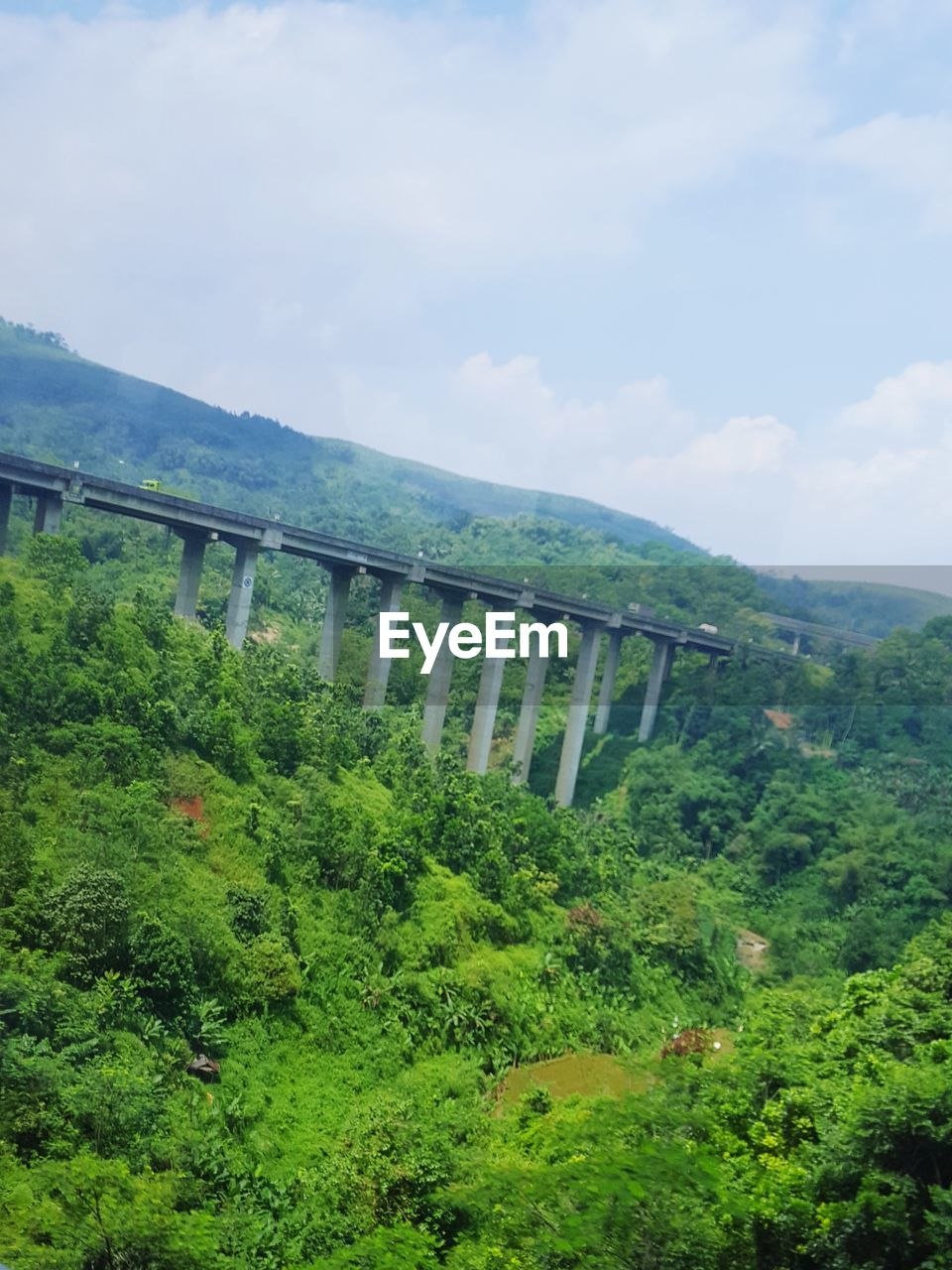 plant, sky, mountain, green color, cloud - sky, nature, environment, tree, scenics - nature, landscape, day, bridge, growth, no people, beauty in nature, foliage, built structure, transportation, lush foliage, tranquil scene, bridge - man made structure, outdoors