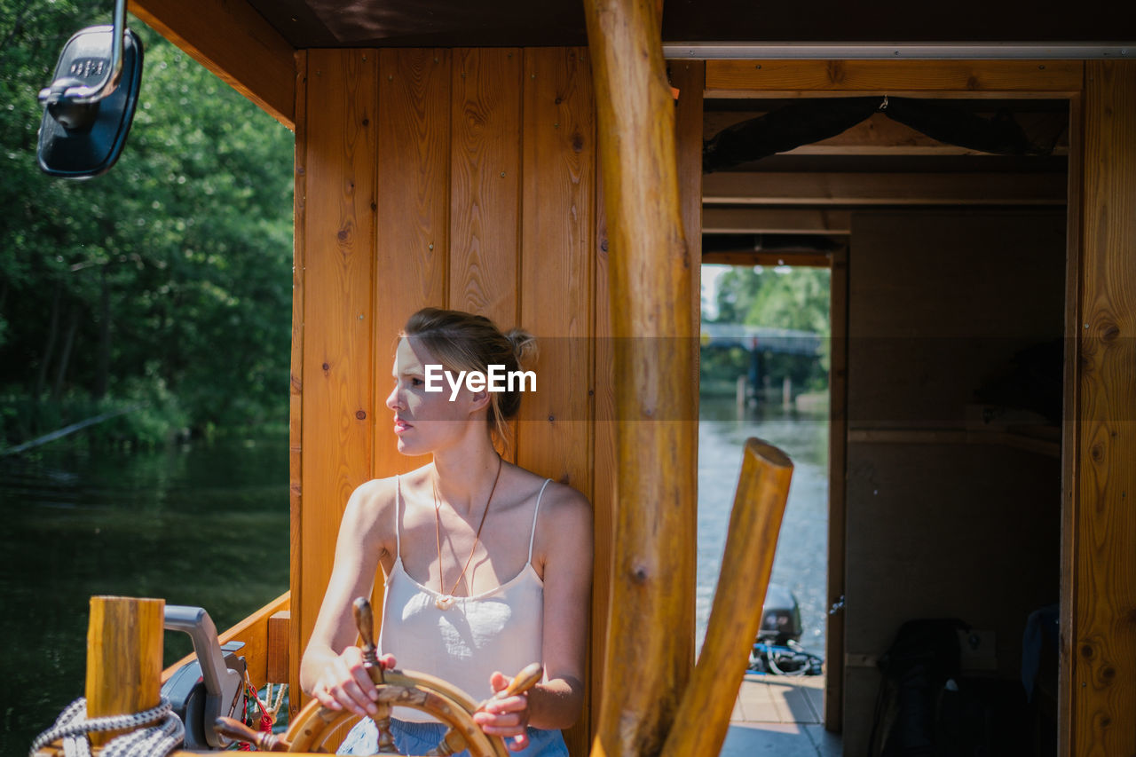 Woman Sitting By Wheel In Boat On Lake
