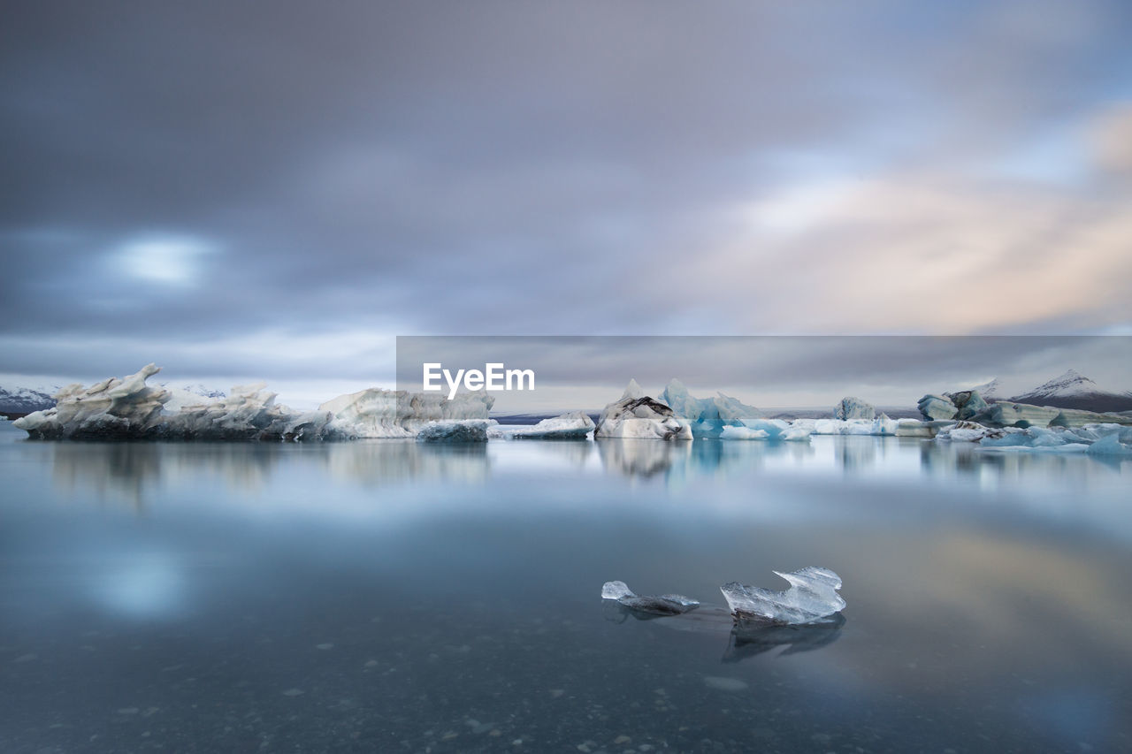 Scenic View Of Frozen Lake Against Cloudy Sky