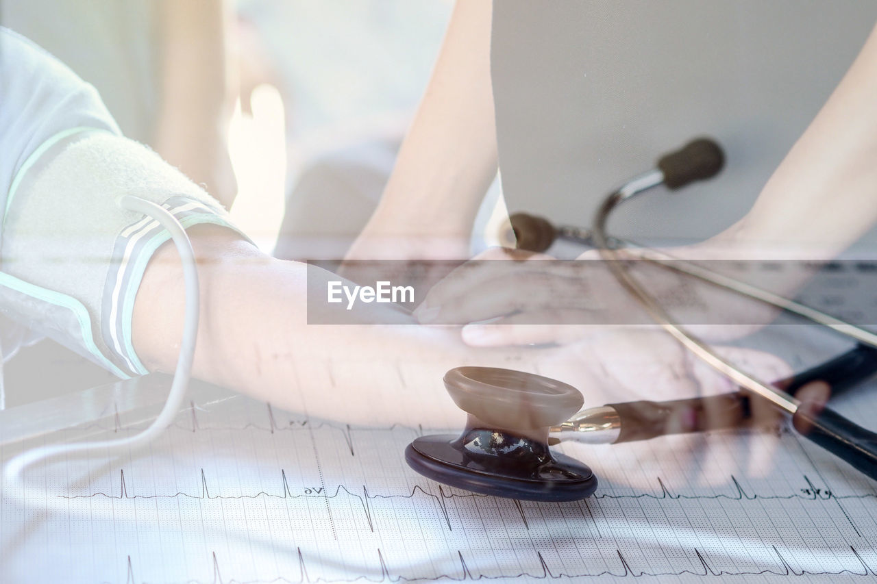 Double Exposure Image Of Doctor With Patient And Pulse Trace
