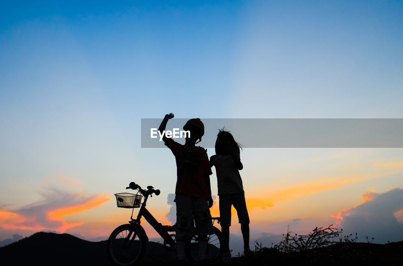 sunset, two people, photography themes, bicycle, silhouette, photographing, real people, sky, camera - photographic equipment, men, togetherness, leisure activity, nature, outdoors, tranquil scene, technology, beauty in nature, selfie, portable information device, mobile phone, lifestyles, scenics, standing, wireless technology, full length, women, bonding, photo messaging, friendship, day, people