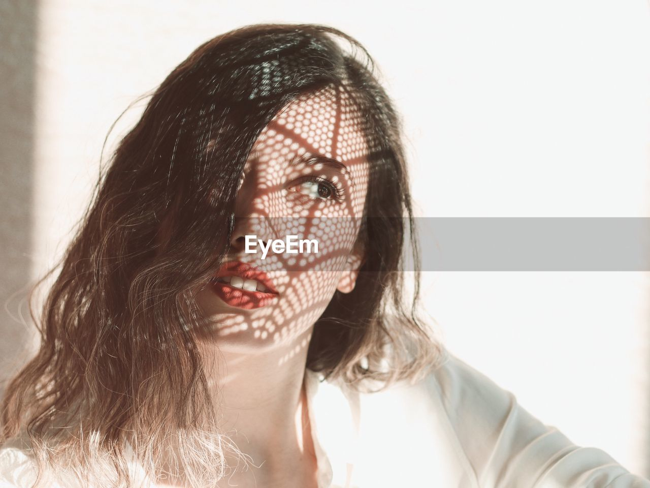 Beautiful Woman With Shadow On Face Against Wall