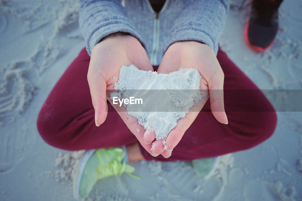 one person, human hand, real people, heart shape, human body part, women, holding, hand, love, high angle view, positive emotion, child, leisure activity, lifestyles, emotion, midsection, day, winter, childhood, outdoors, warm clothing
