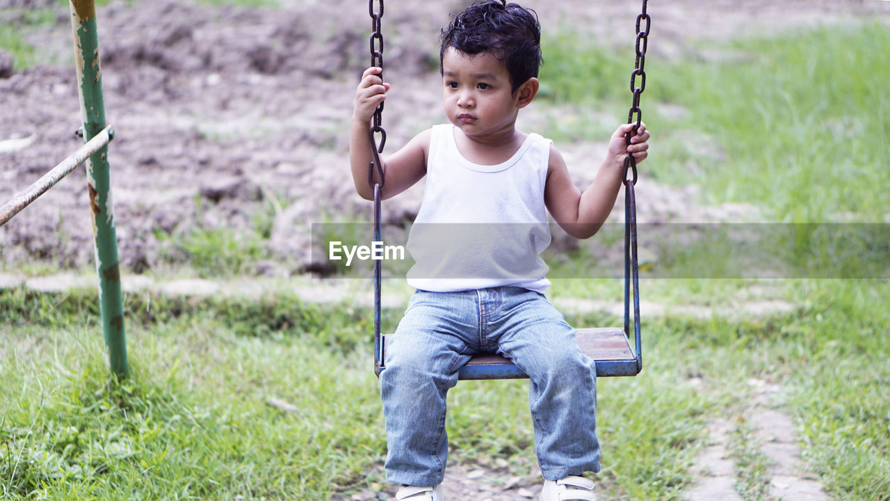 child, childhood, front view, one person, casual clothing, full length, leisure activity, playground, males, boys, real people, men, sitting, swing, looking at camera, lifestyles, focus on foreground, portrait, holding, innocence, outdoors, outdoor play equipment