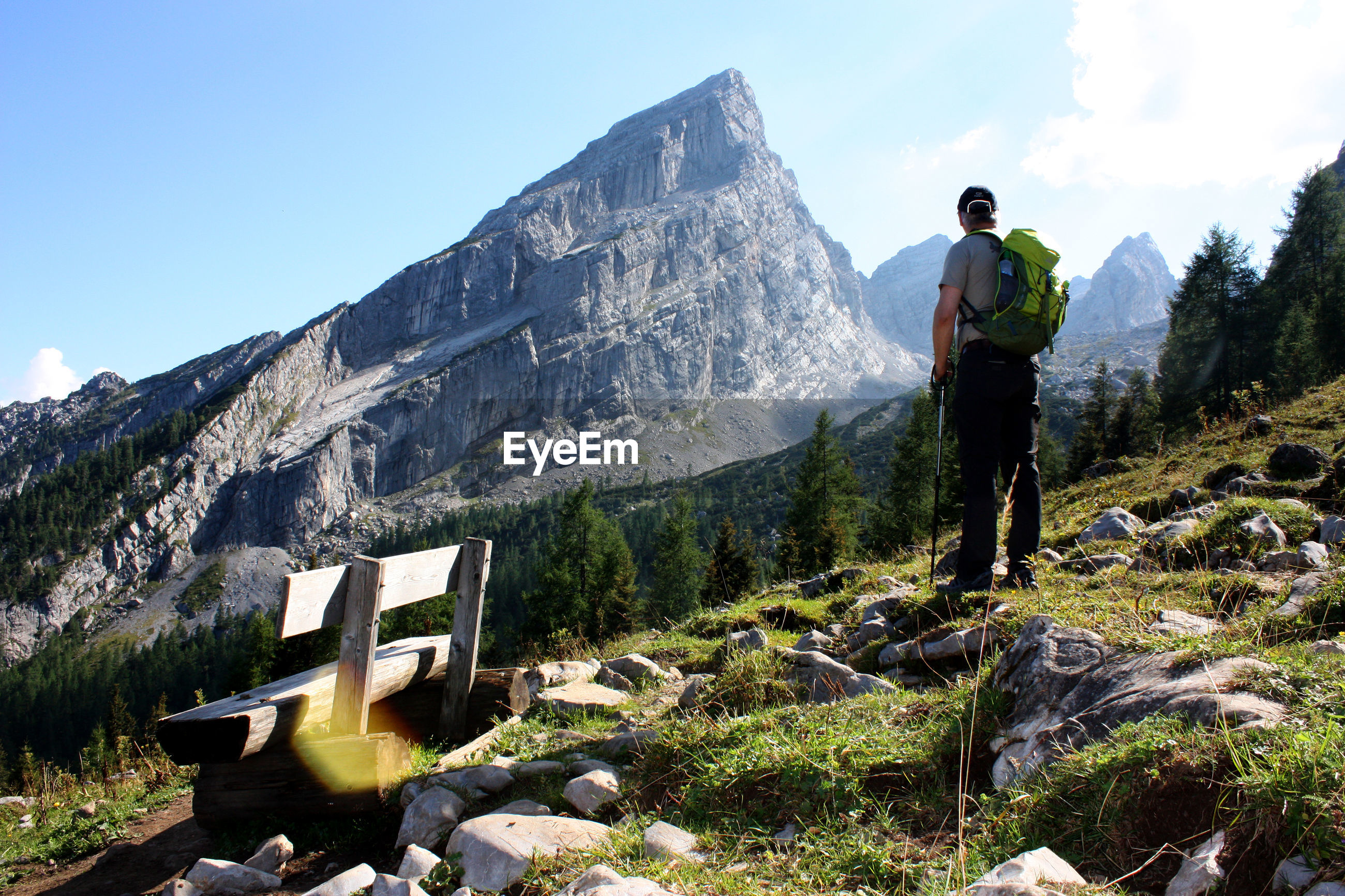 Rear view of hiker standing on field against mountain