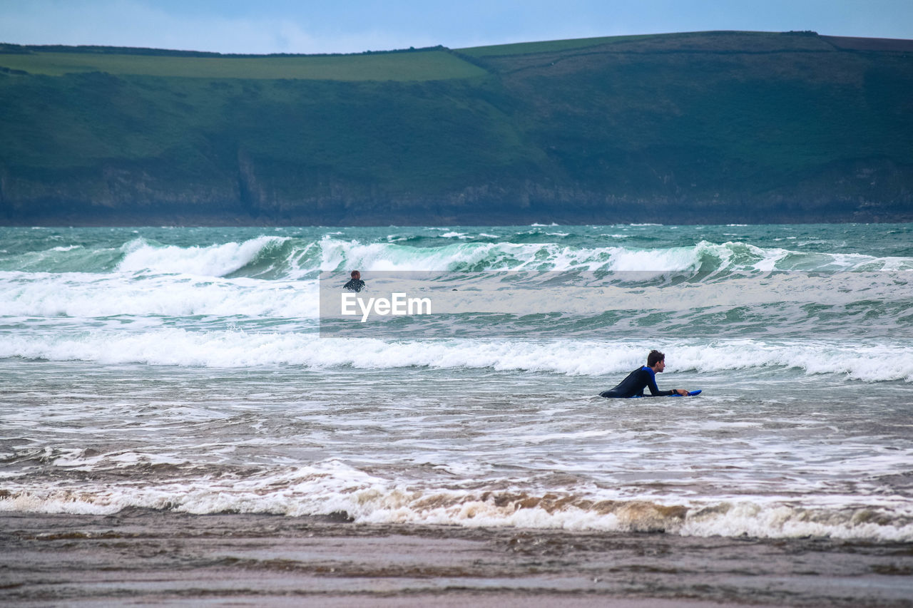 wave, real people, extreme sports, leisure activity, surfing, motion, nature, sport, men, sea, skill, one person, adventure, scenics, beauty in nature, lifestyles, water, fun, day, vacations, outdoors, beach, mountain, sky, one man only, people