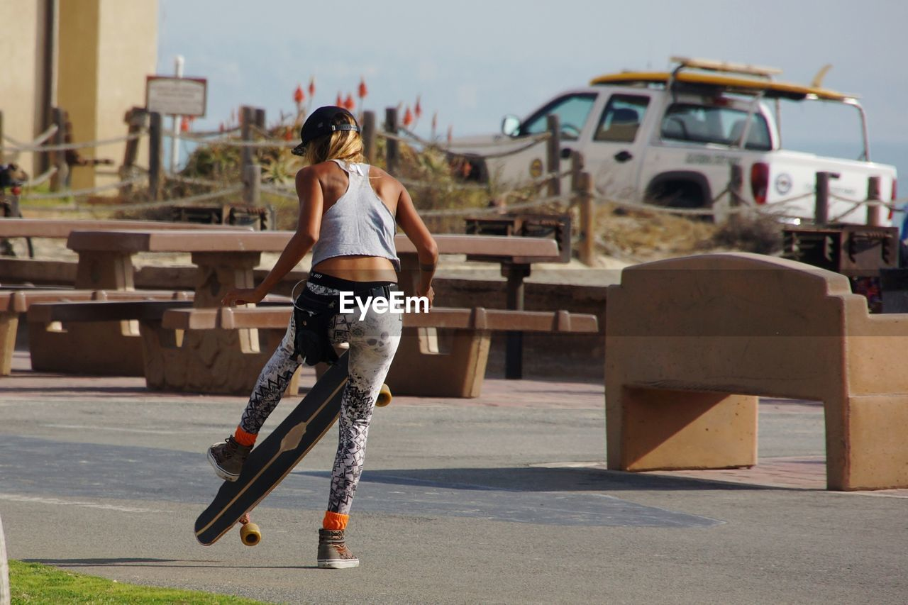 Rear View Of Young Woman With Skateboard Standing On Road In City