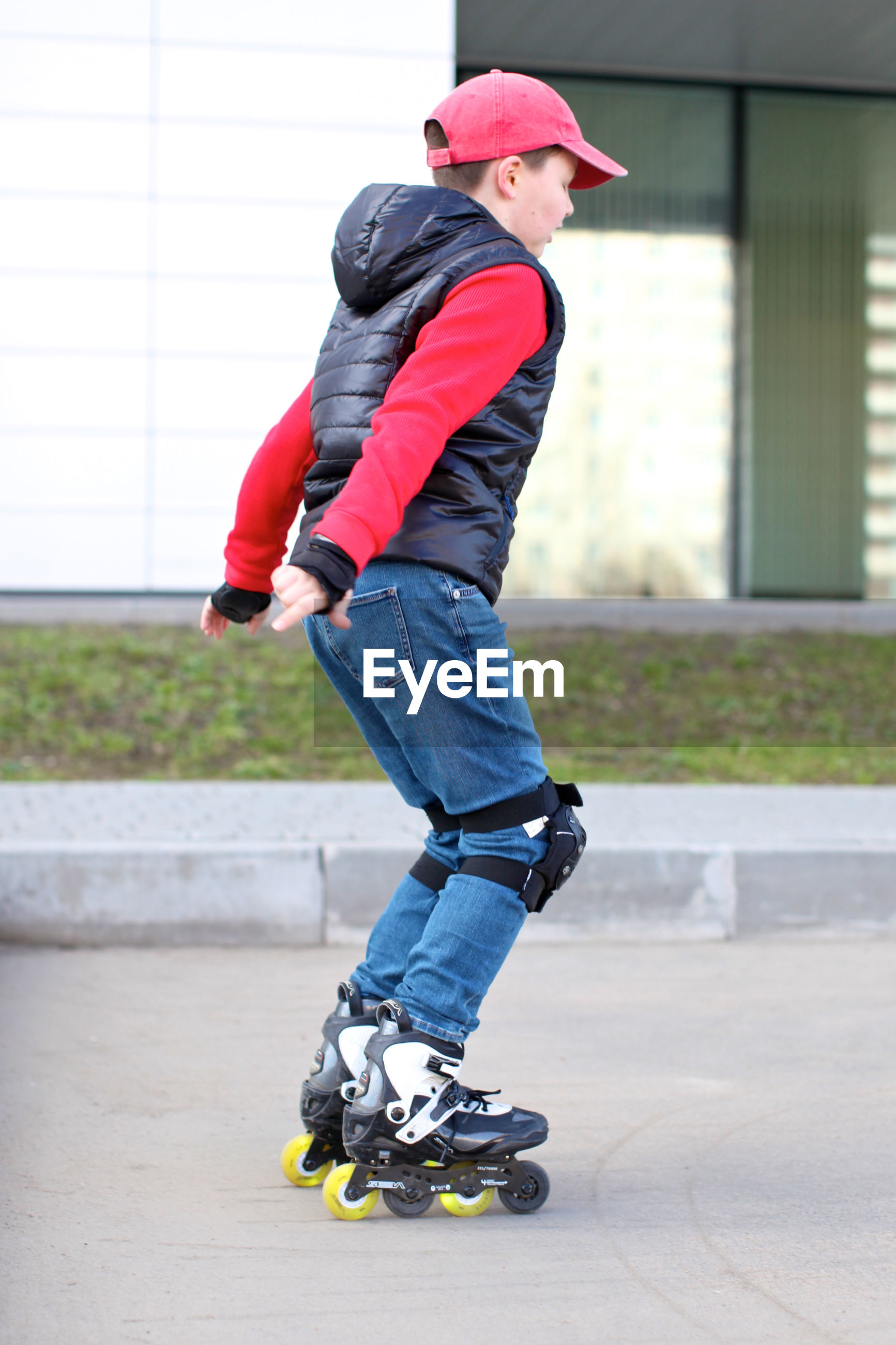Full length of boy skateboarding on street in city