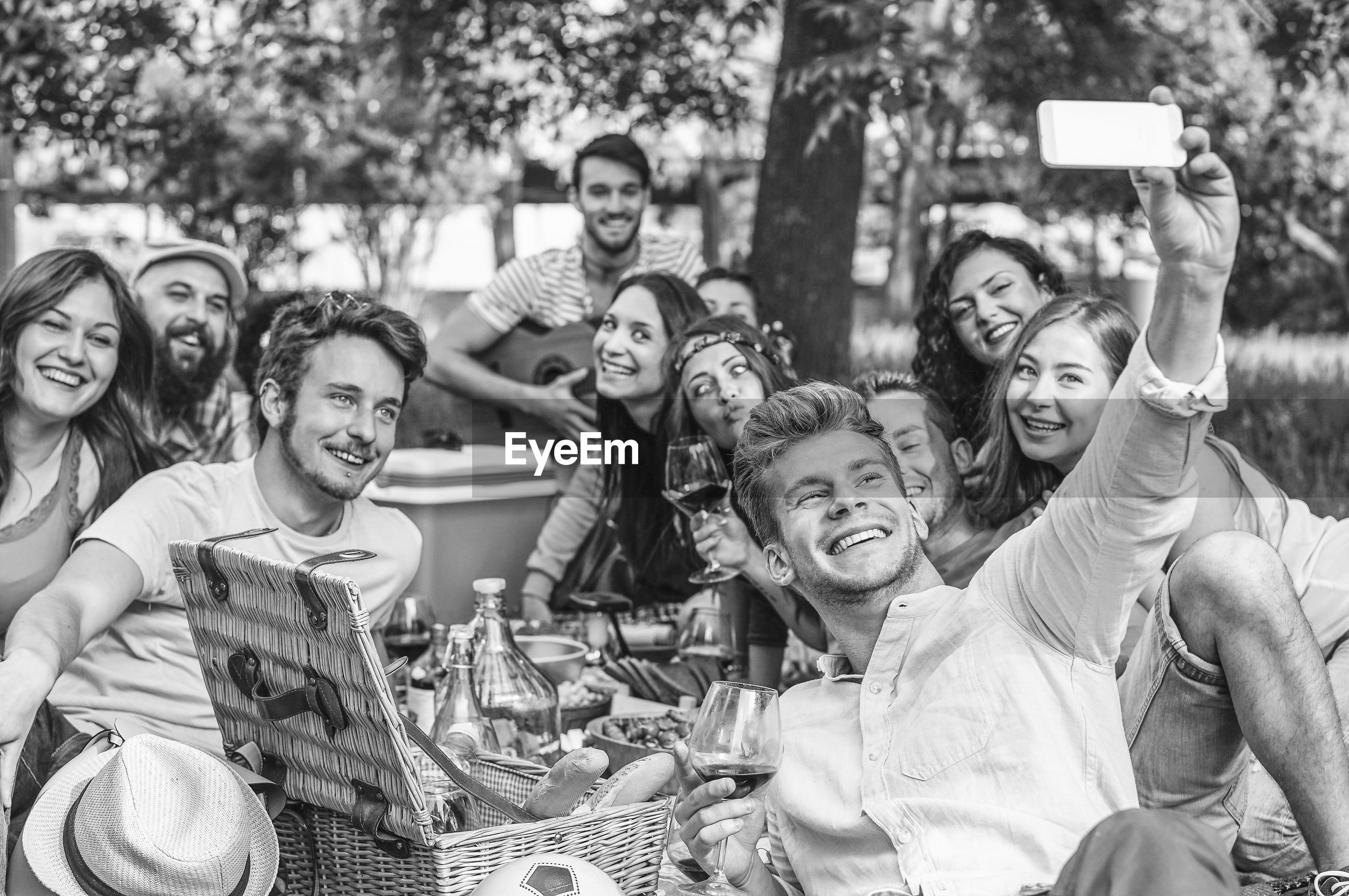 Man taking selfie on mobile phone with friends in picnic
