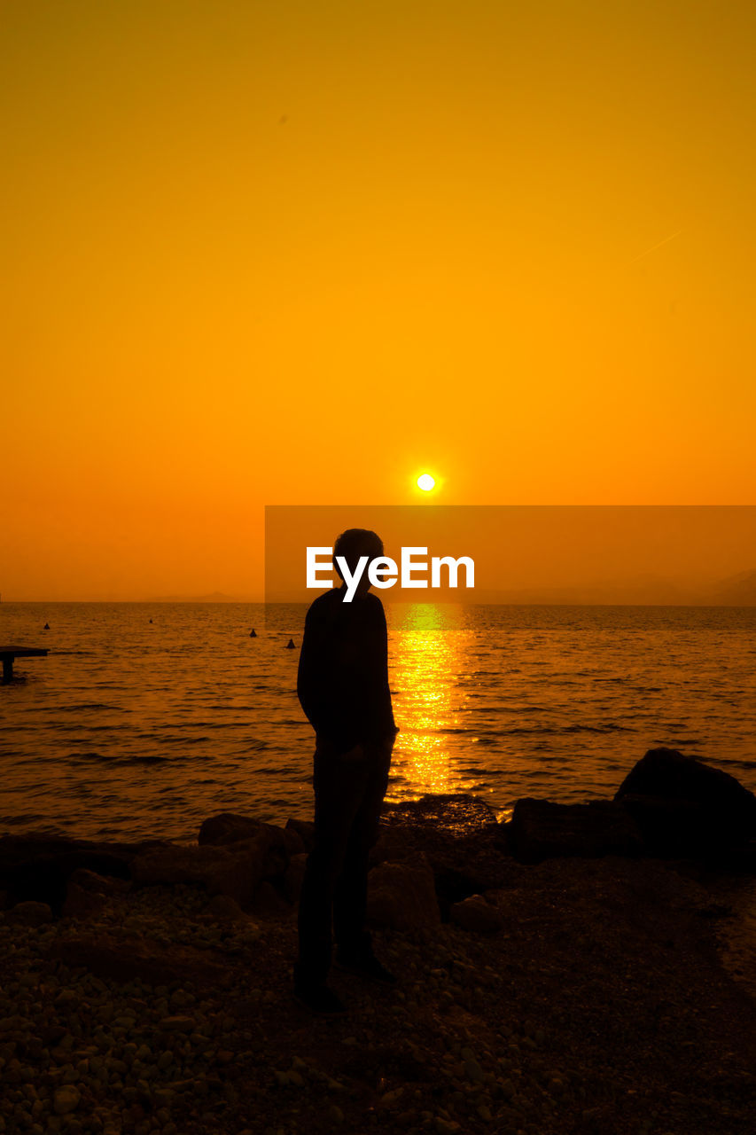 Silhouette Man Standing At Beach Against Clear Orange Sky