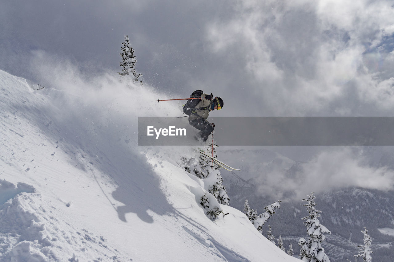 Man Jumping On Snow Covered Mountain Against Sky
