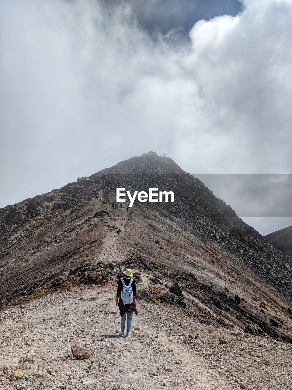 mountain, sky, leisure activity, real people, hiking, cloud - sky, non-urban scene, lifestyles, day, nature, environment, scenics - nature, adventure, beauty in nature, rear view, activity, landscape, one person, mountain range, travel, outdoors