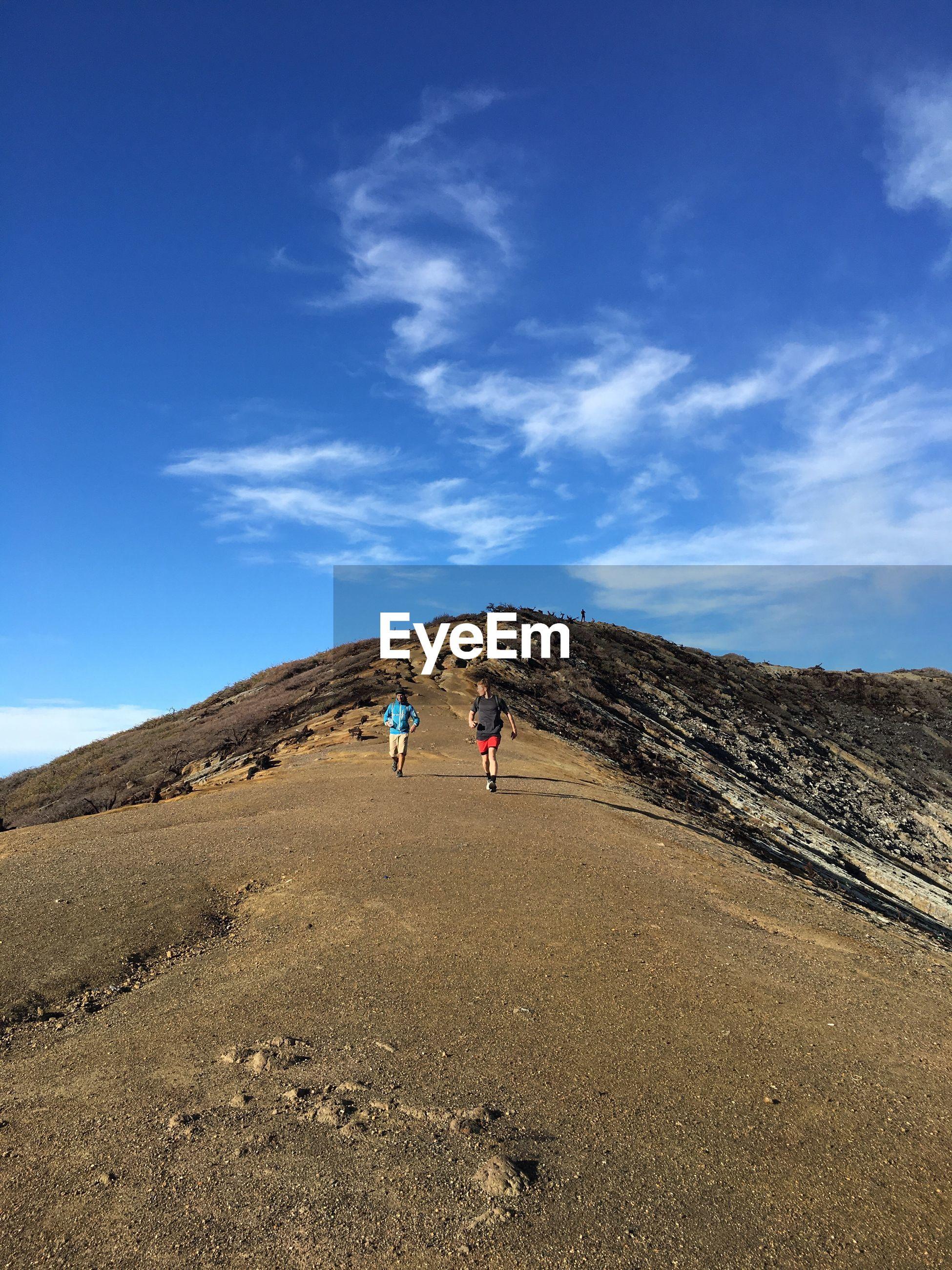 Men walking on mountain against blue sky