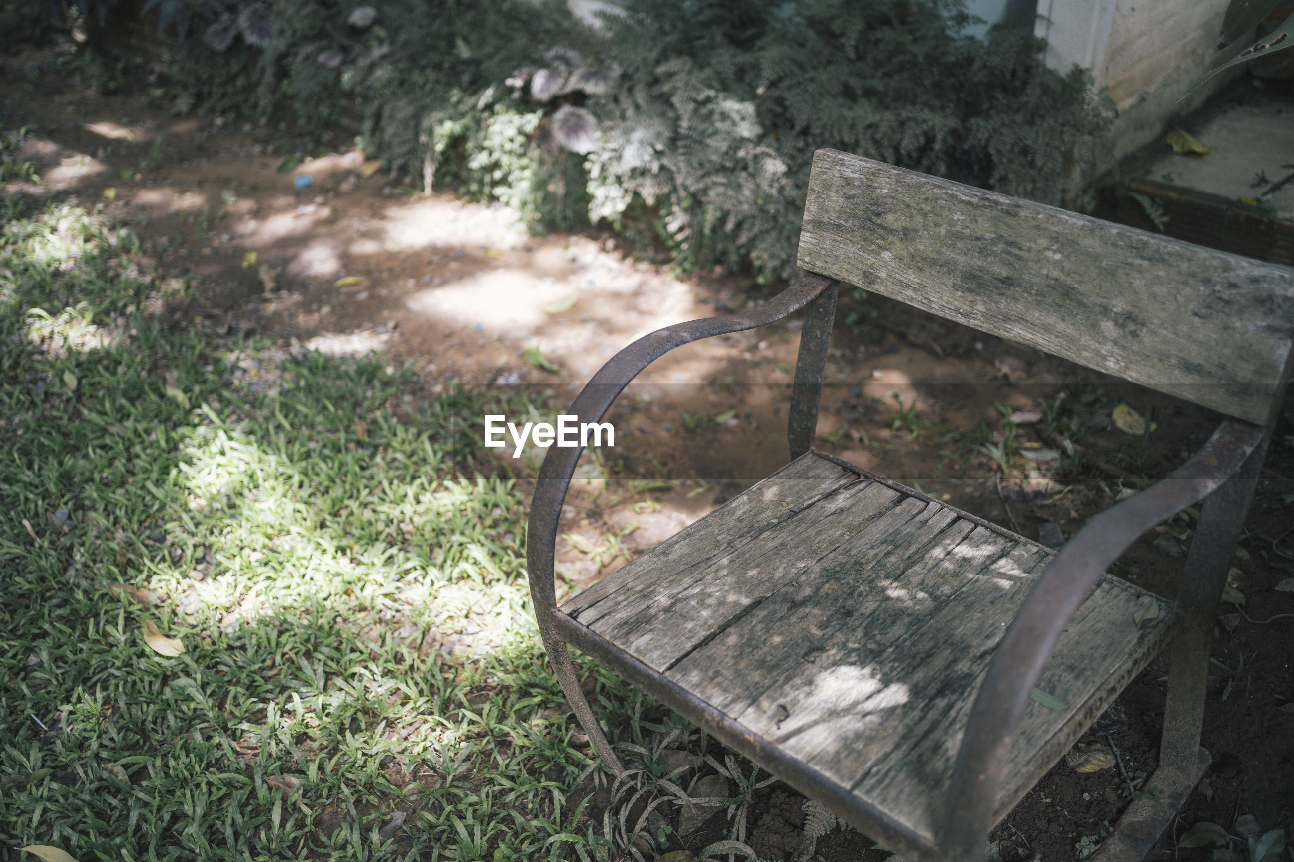 HIGH ANGLE VIEW OF PARK BENCH IN GARDEN