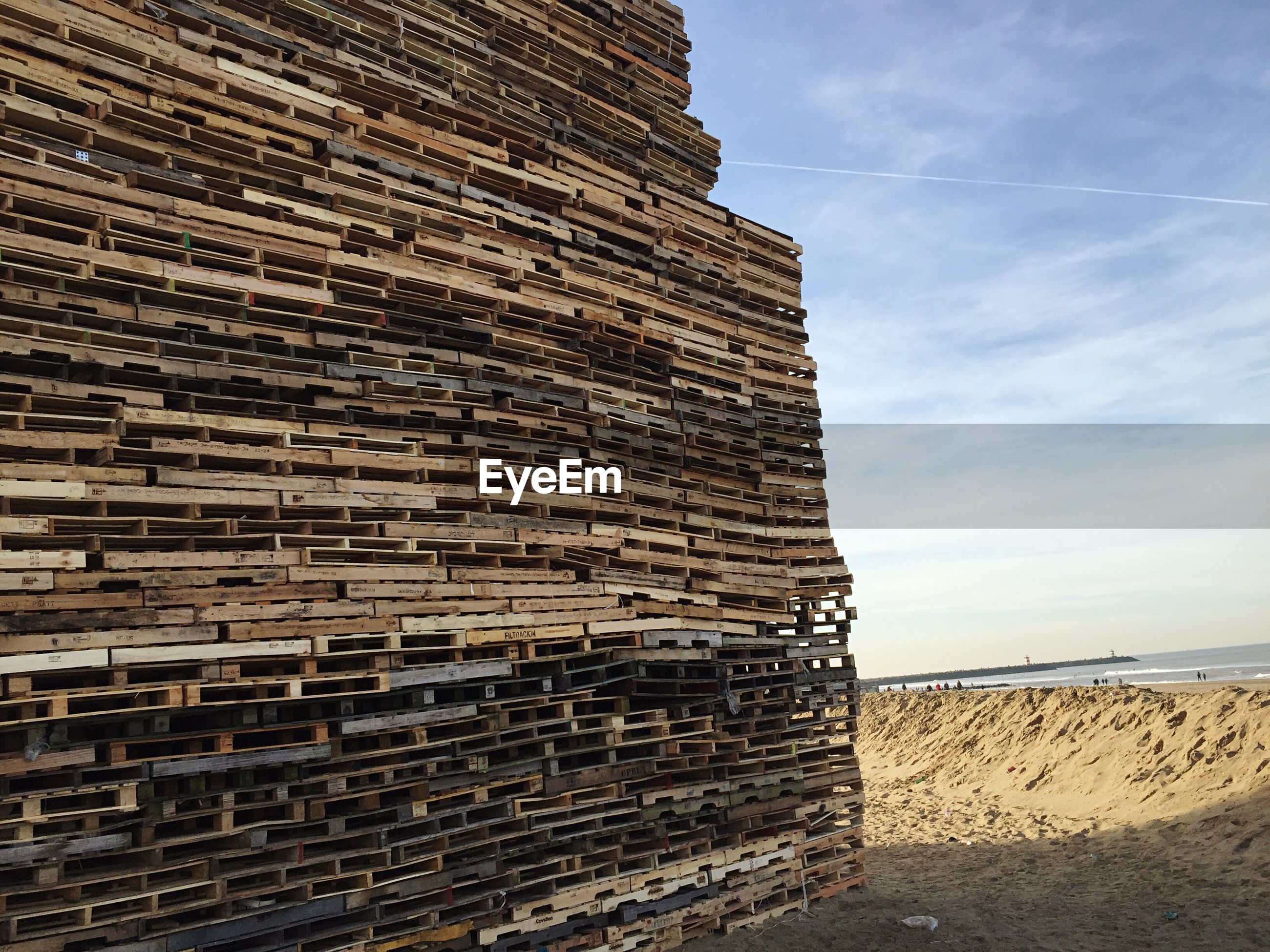Stack of wooden pallets at beach against sky