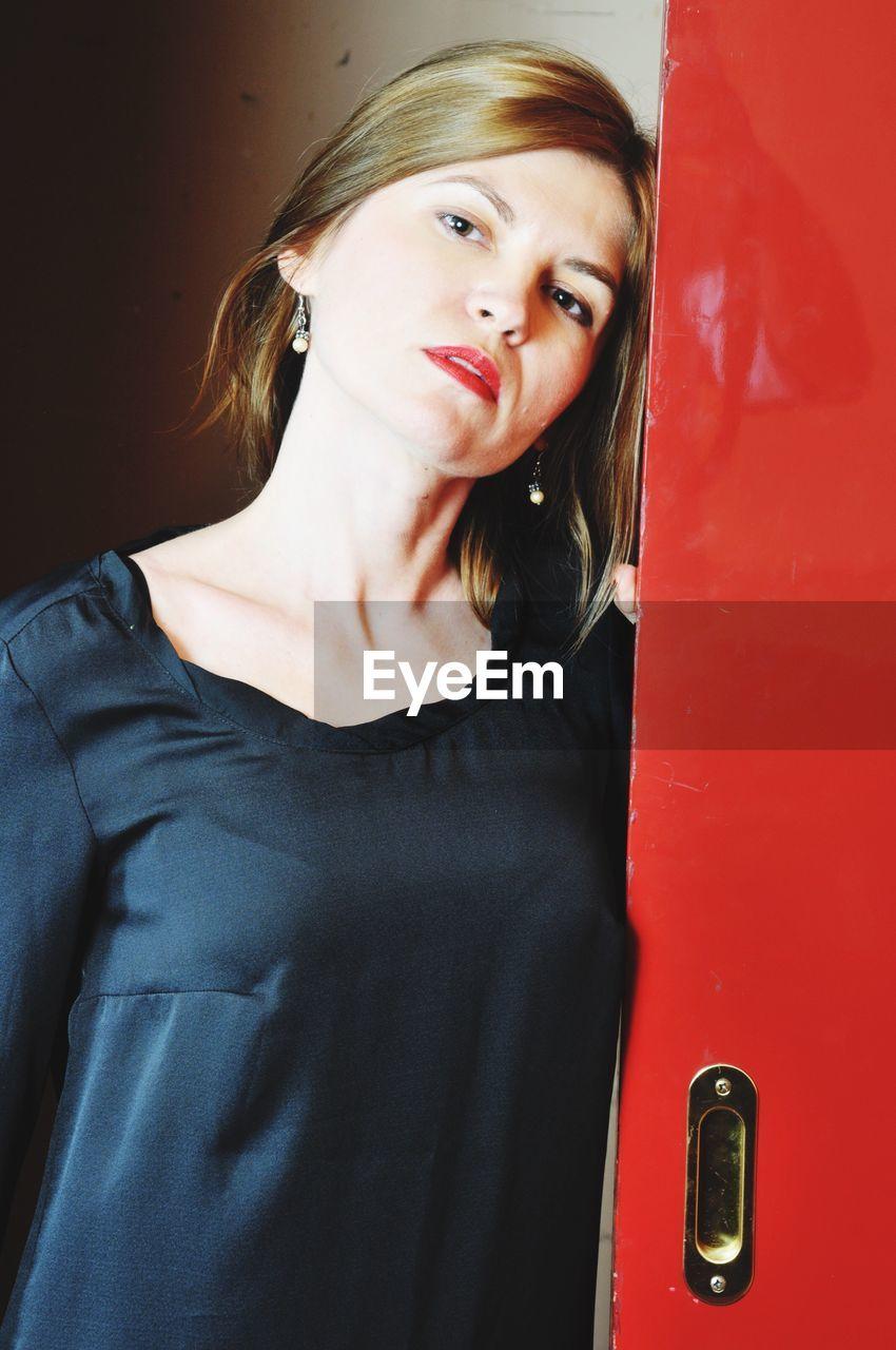 Portrait Of Beautiful Woman Standing By Door