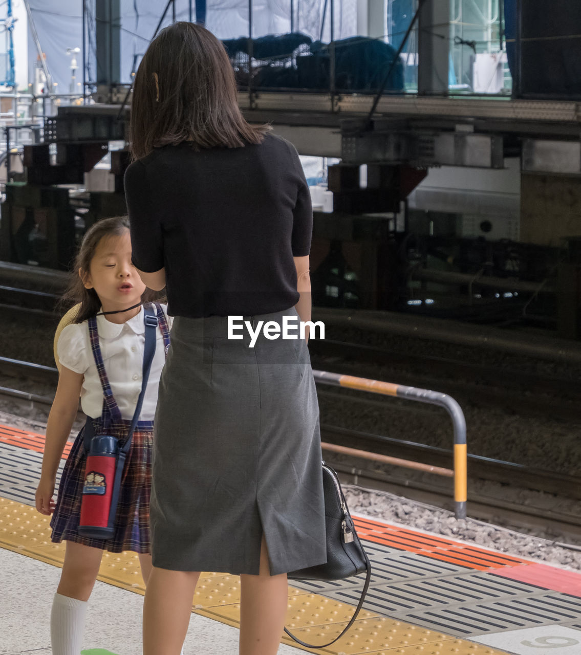 REAR VIEW OF MOTHER AND DAUGHTER ON FLOOR AGAINST BUS
