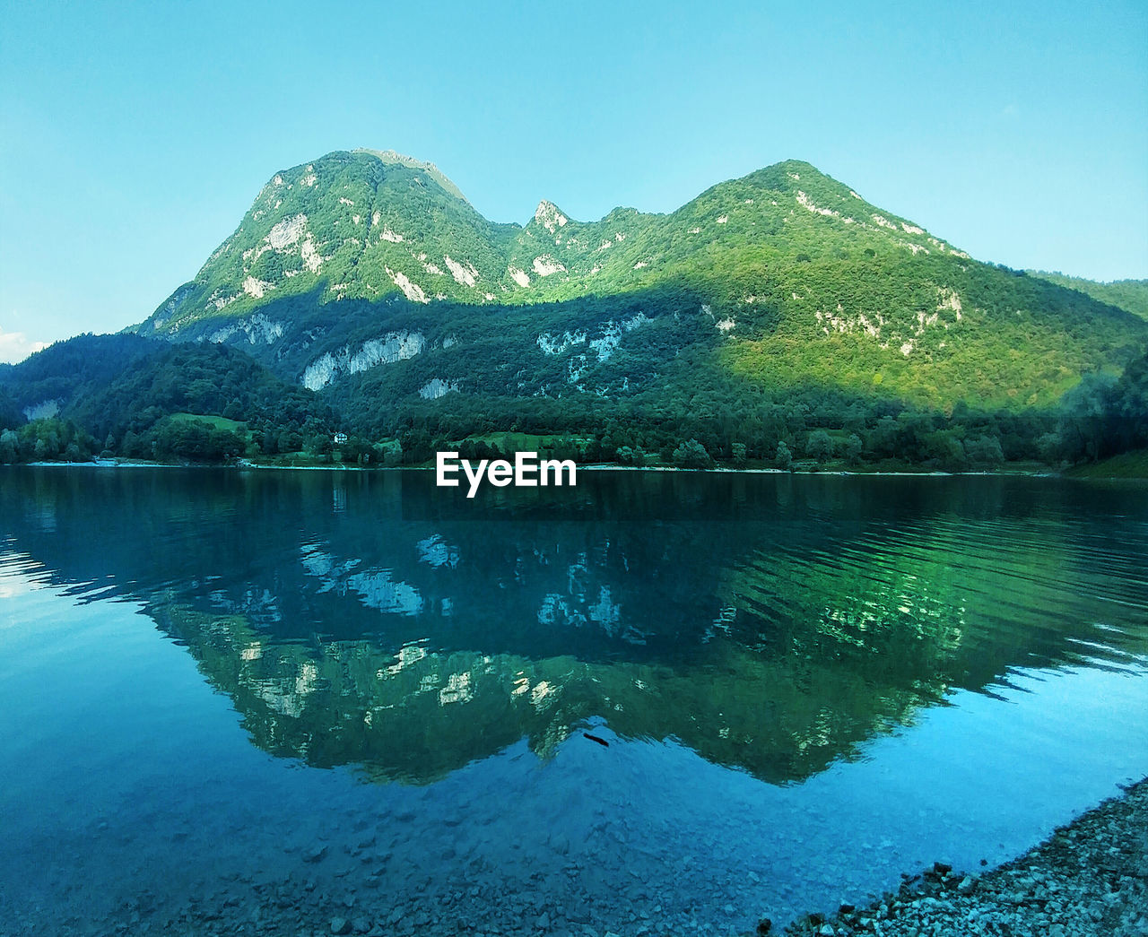 mountain, reflection, lake, water, mountain range, tranquil scene, scenics, tranquility, nature, beauty in nature, idyllic, waterfront, outdoors, no people, day, clear sky, sky, symmetry, travel destinations, tree