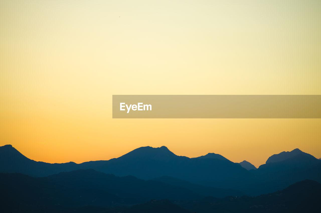 Silhouette of mountain range against sky at sunrise