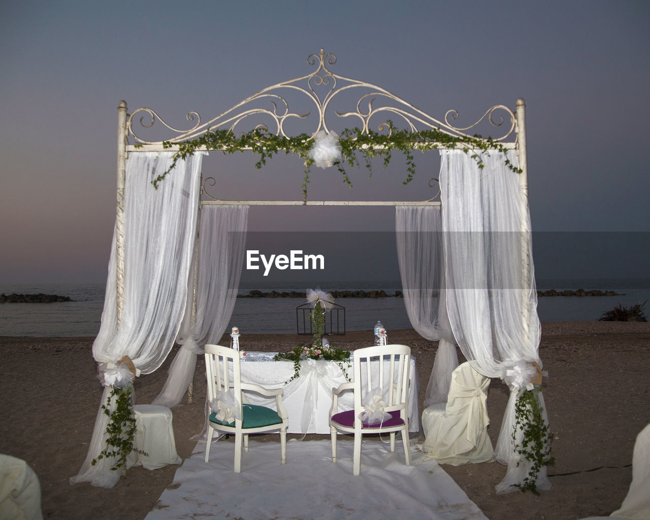 seat, chair, table, white color, nature, curtain, decoration, sky, no people, wedding, absence, tablecloth, event, setting, celebration, place setting, plant, furniture, beach, water, outdoors, wedding ceremony, luxury