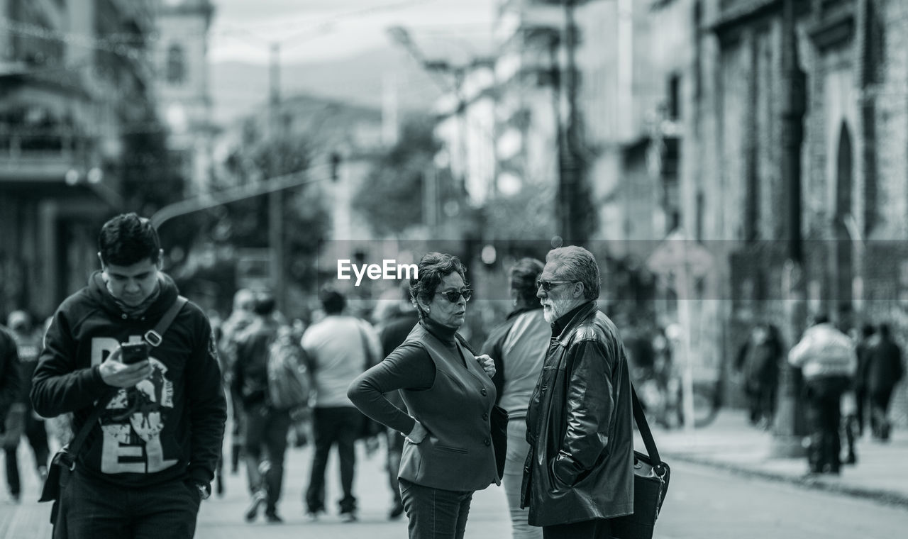 city, real people, street, men, focus on foreground, incidental people, group of people, architecture, people, lifestyles, day, adult, building exterior, women, three quarter length, walking, city life, casual clothing, built structure, standing, outdoors, warm clothing