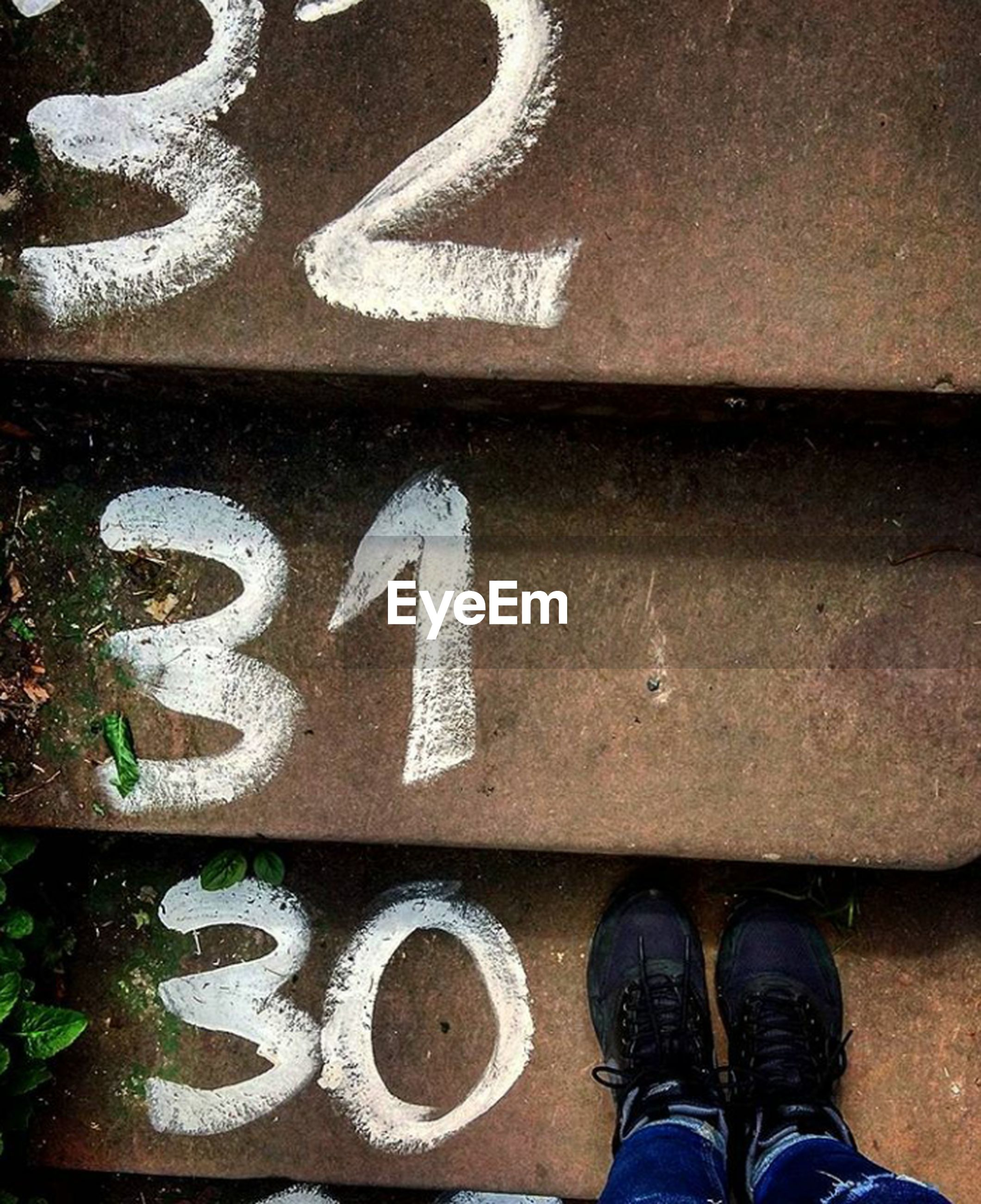 shoe, low section, person, standing, human foot, personal perspective, communication, western script, footwear, close-up, outdoors, day, full frame