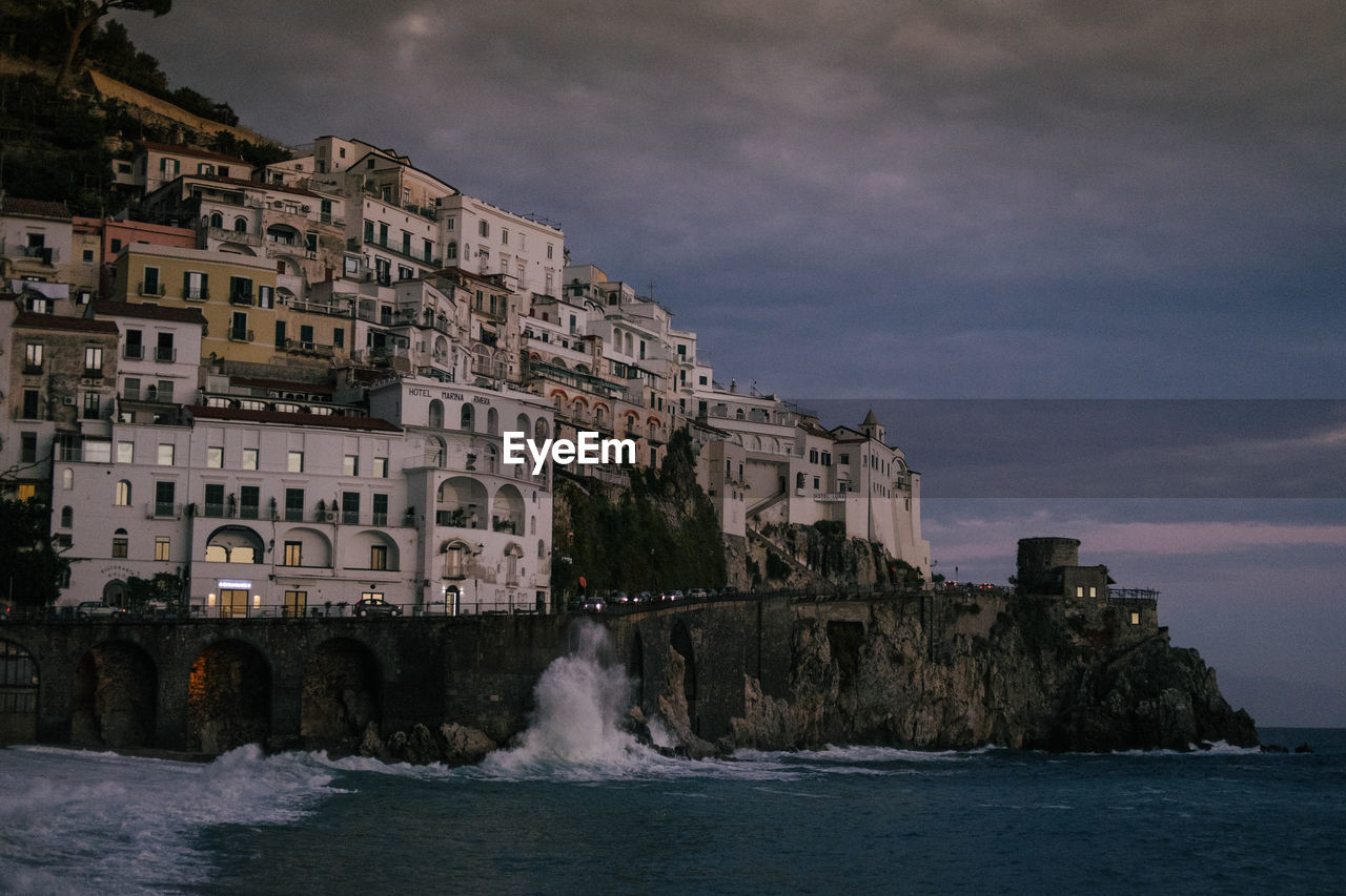 water, architecture, building exterior, built structure, sky, cloud - sky, sea, motion, nature, building, waterfront, aquatic sport, beauty in nature, city, sport, wave, no people, scenics - nature, outdoors, power in nature, flowing water