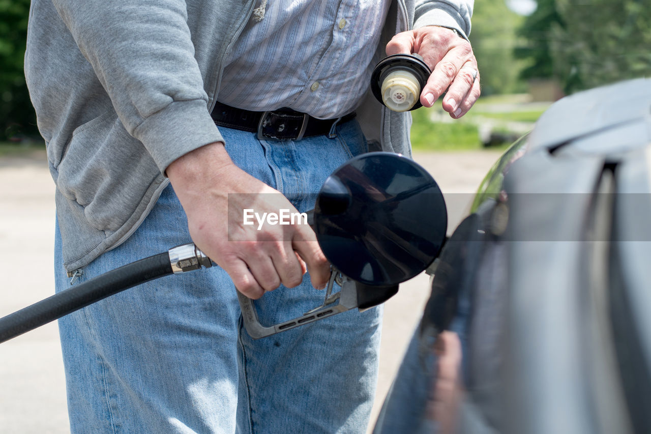 Man uses a gas nozzle and hose to fill his vehicle with fuel as a gas station in the usa