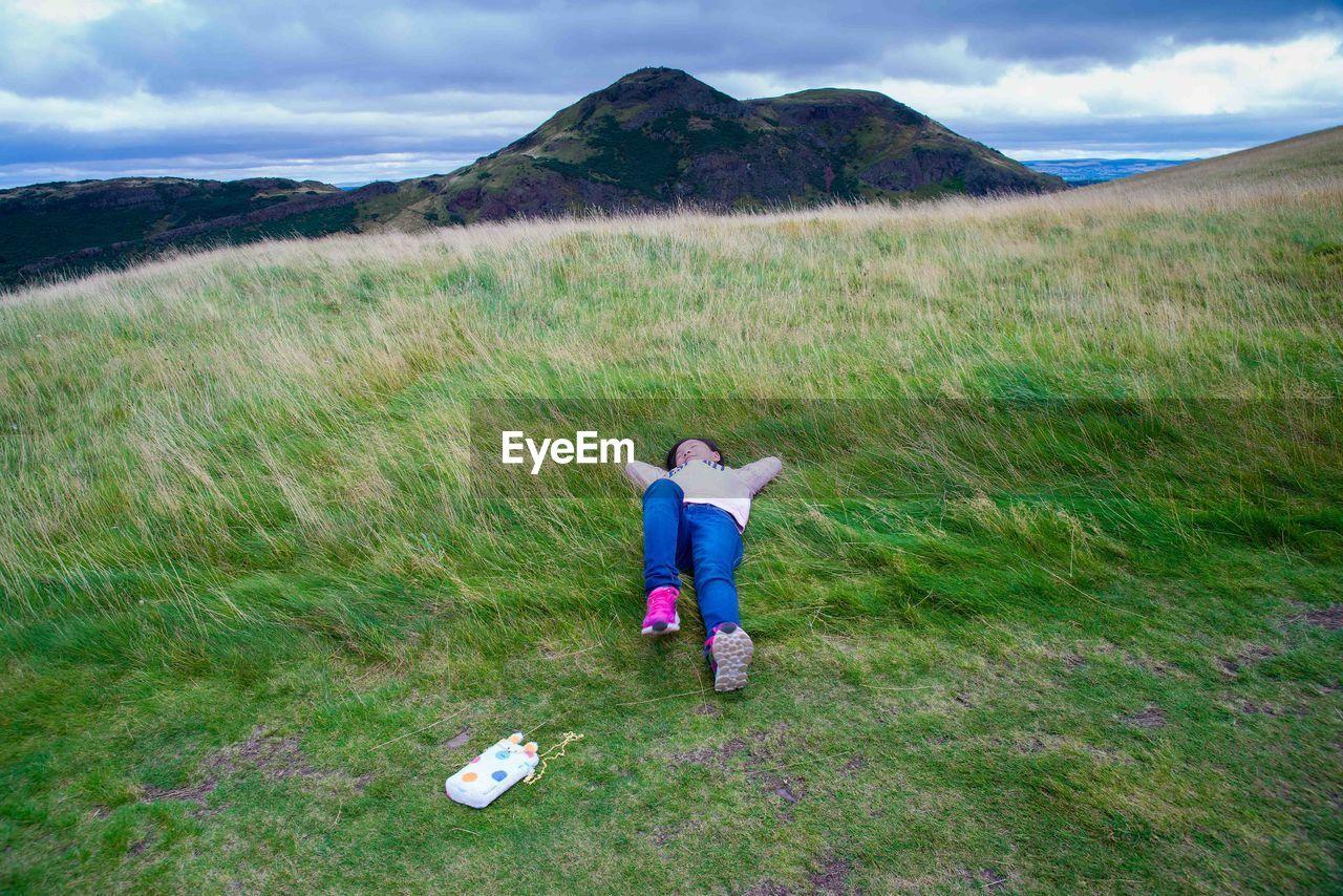 Full Length Of Girl Relaxing On Grassy Field Against Cloudy Sky