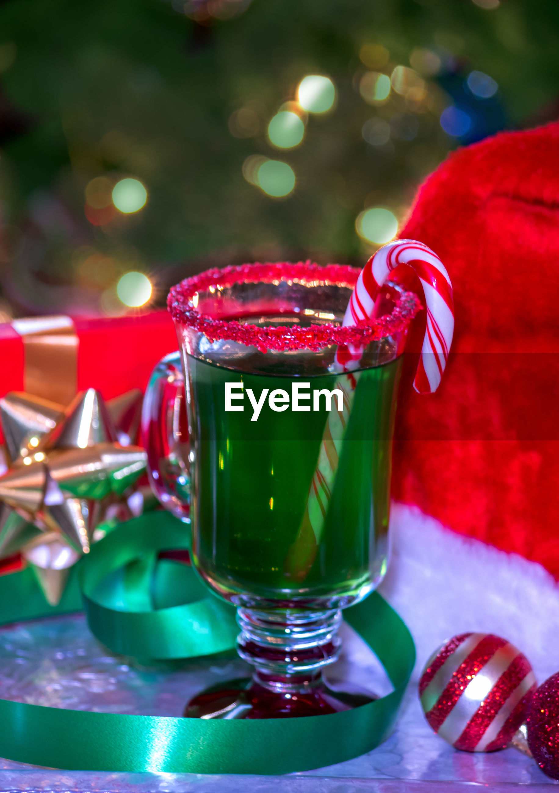holiday drink  is green punch with a red sugar rim and a candy cane garnish