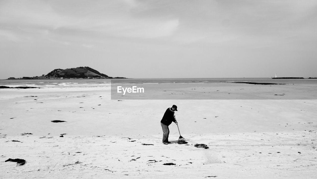 Man Sweeping At Beach Against Sky