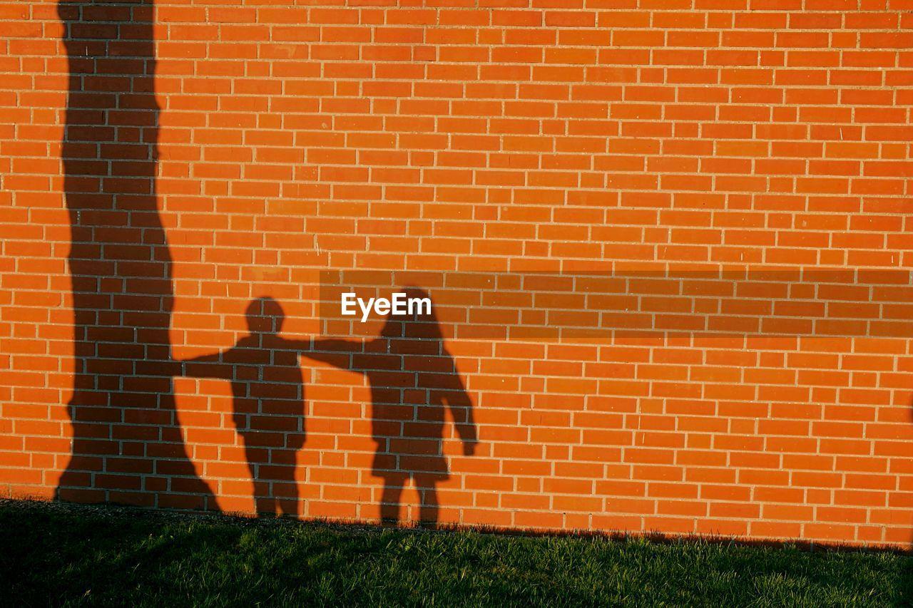 Shadow of children on brick wall