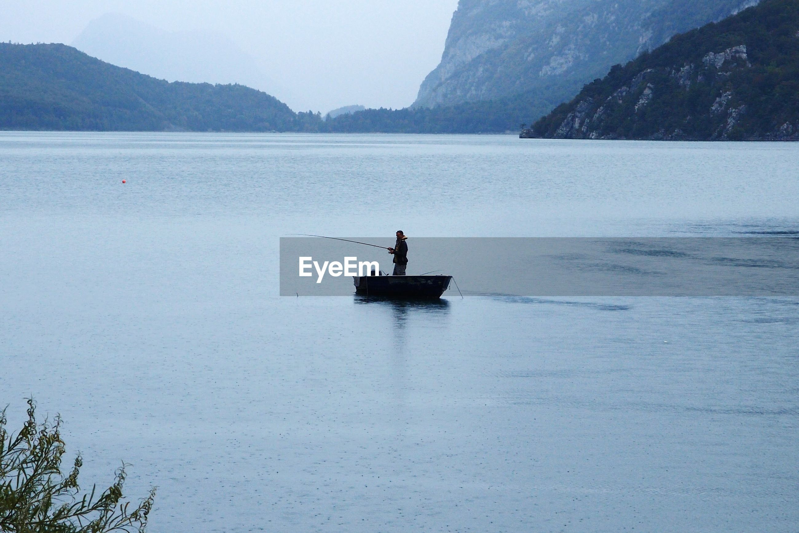 Person fishing while standing on boat in lake