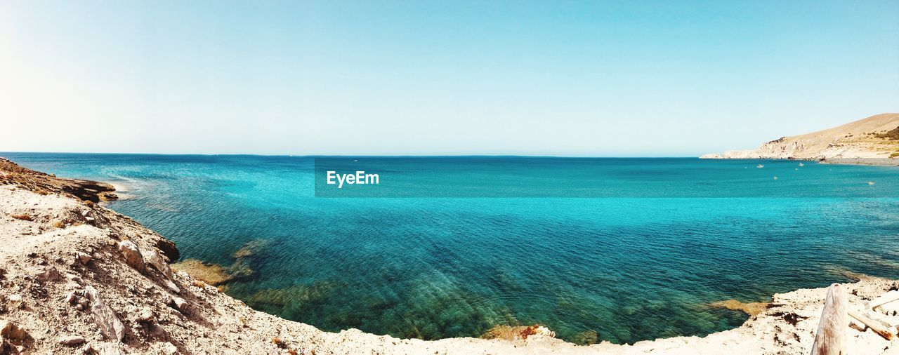 sea, scenics - nature, water, sky, beauty in nature, tranquil scene, horizon over water, horizon, blue, tranquility, land, beach, clear sky, nature, day, idyllic, rock, copy space, no people, outdoors, turquoise colored, rocky coastline
