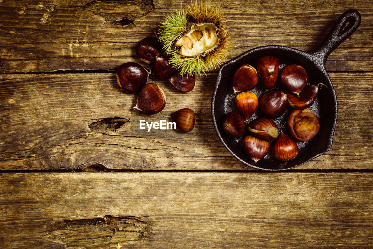 food and drink, food, healthy eating, fruit, freshness, wood - material, wellbeing, table, directly above, still life, indoors, bowl, no people, high angle view, chestnut - food, brown, large group of objects, kitchen utensil, nut - food, chestnut