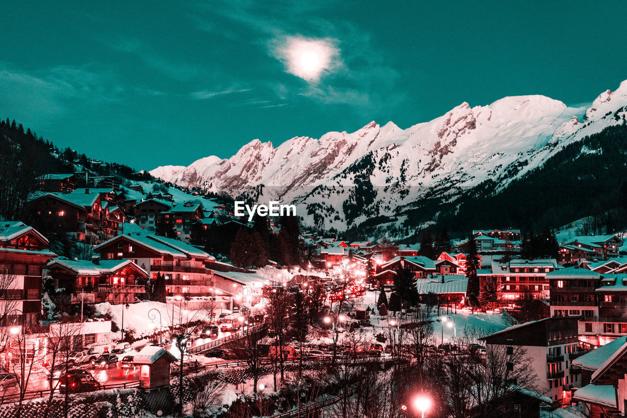 mountain, cold temperature, snow, winter, architecture, built structure, building exterior, mountain range, sky, beauty in nature, building, nature, scenics - nature, snowcapped mountain, city, plant, no people, tree, illuminated, outdoors