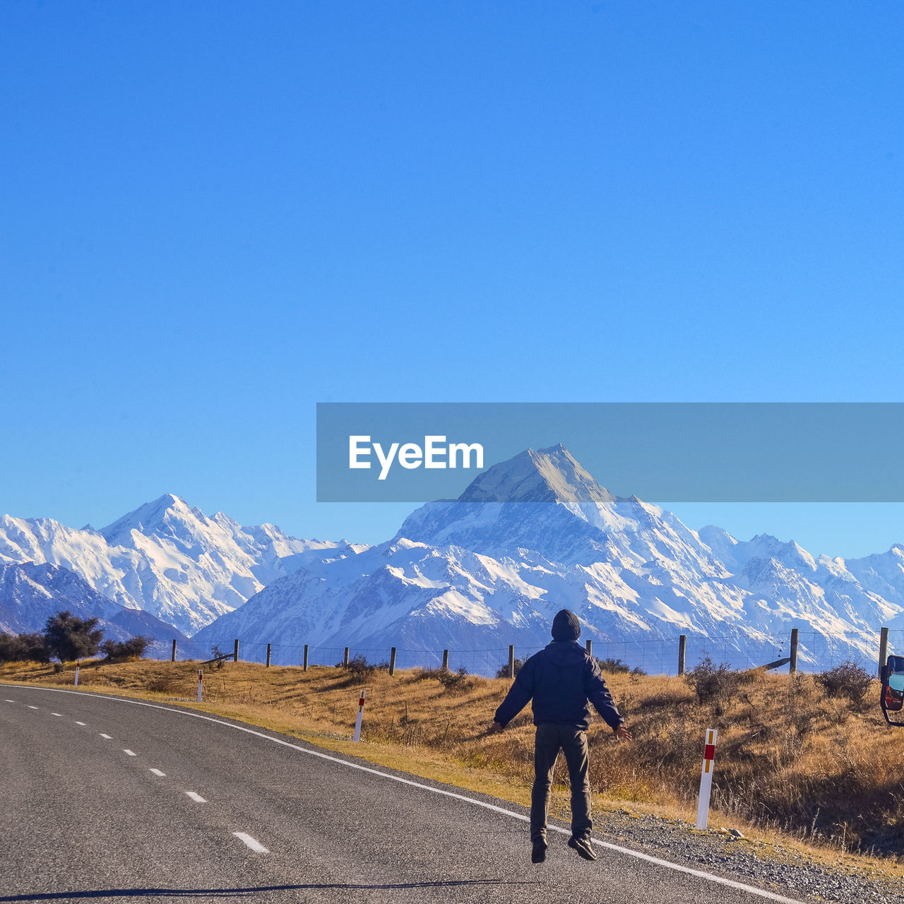 Rear View Of Man Against Snowcapped Mountain And Clear Sky