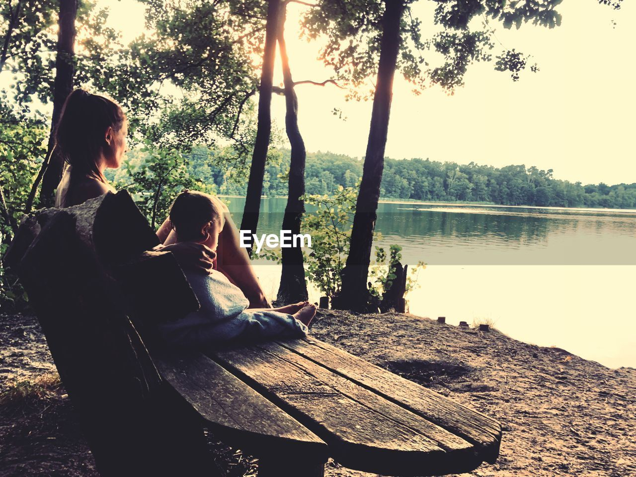 Rear view of mother and daughter sitting on bench by lake