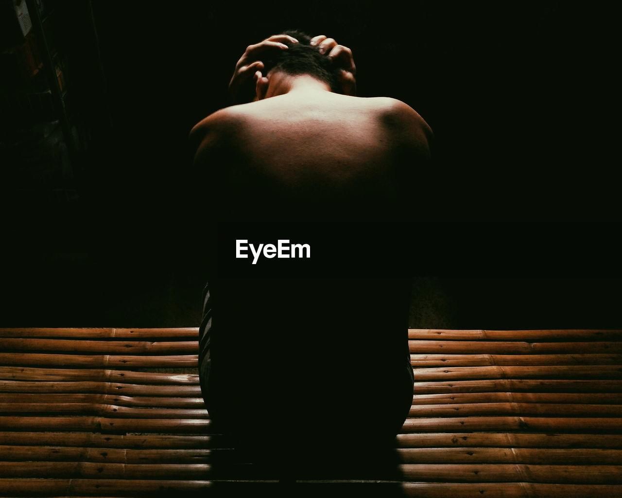 Rear View Of Shirtless Depressed Man Sitting In Darkroom