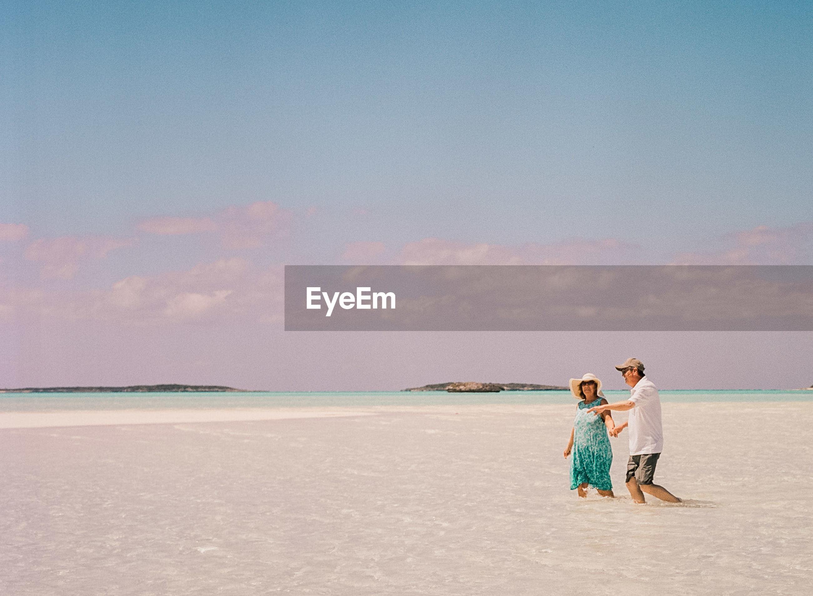 Couple walking in sea against sky