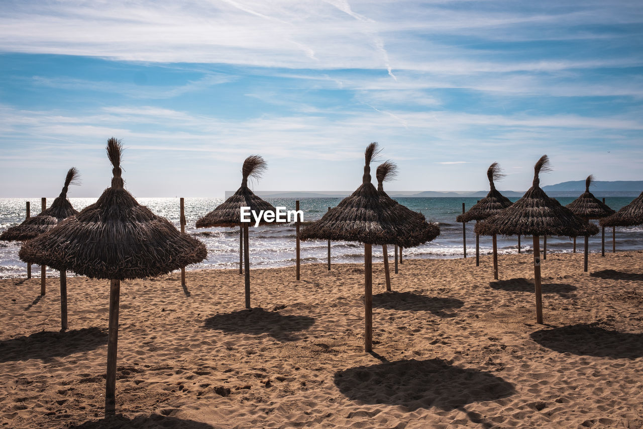 beach, land, sky, cloud - sky, thatched roof, water, beauty in nature, nature, sea, scenics - nature, roof, tranquility, tranquil scene, sand, day, no people, sunlight, umbrella, parasol, outdoors, horizon over water
