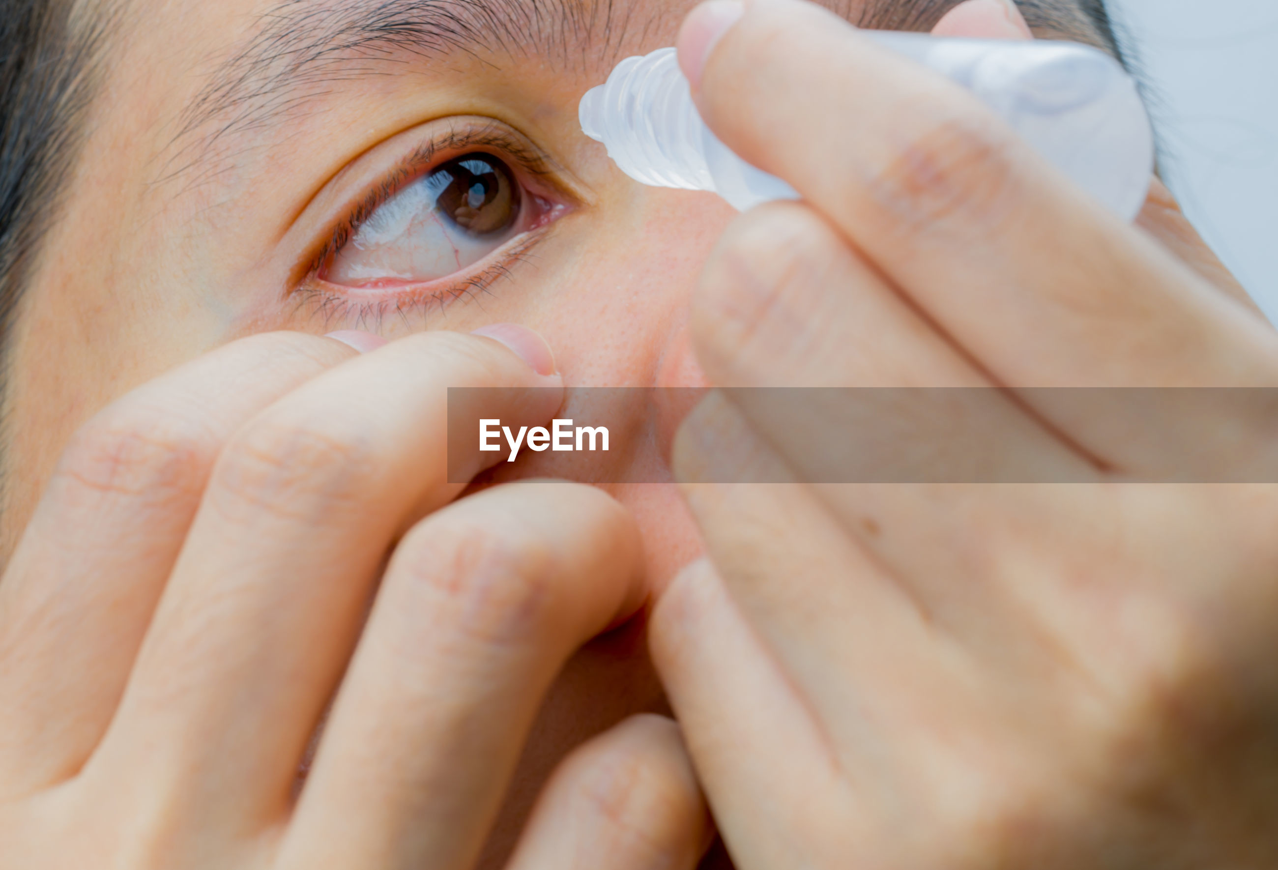 Close-up of woman putting drop in eye