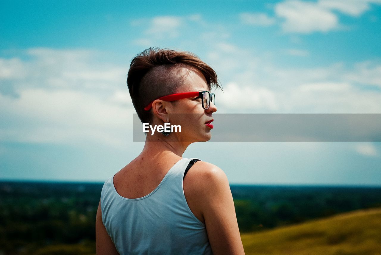 Rear View Of Thoughtful Young Woman Looking Away While Standing Against Blue Sky