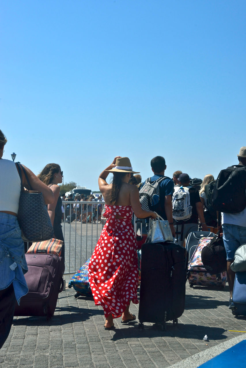 group of people, clear sky, real people, men, rear view, women, people, sky, crowd, copy space, sunlight, adult, day, nature, leisure activity, clothing, lifestyles, togetherness, blue, outdoors
